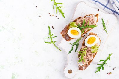 Toasts with tuna. Italian bruschetta sandwiches with canned tuna, egg and cucumber. Top view, flat lay, copy space