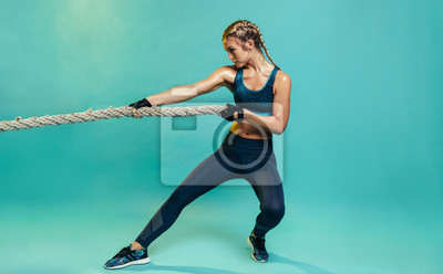 Plakat Tough sports woman exercising with battling rope