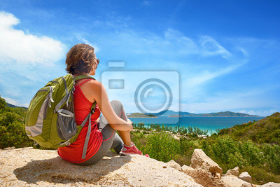 Tourist with backpack relaxing on top of the mountain.