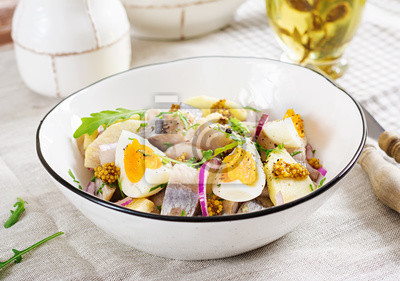 Traditional  salad of salted herring fillet, fresh apples,  red onion  and eggs. Kosher food. Scandinavian cuisine.