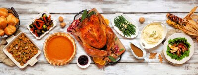 Plakat Traditional Thanksgiving turkey dinner. Above view table scene on a rustic white wood banner background. Turkey, mashed potatoes, stuffing, pumpkin pie and sides.