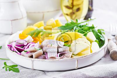 Tradycyjna sałatka z solonego fileta śledziowego, jajek, świeżych jabłek, czerwonej cebuli i ziemniaków. Koszerne jedzenie. Kuchnia skandynawska.