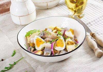 Tradycyjna sałatka z solonego fileta śledziowego, świeżych jabłek, czerwonej cebuli i jajek. Koszerne jedzenie. Kuchnia skandynawska.