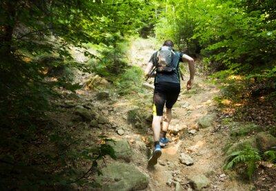 Plakat TrailRunner z plecakiem uruchomiony po stromym wzgórzu