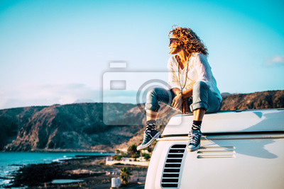 Plakat Travel concept with independent people enjoyig the outdoor leisure activity and wanderlust life lifestyle - woman sit down on the roof of a old nice vintage camper van