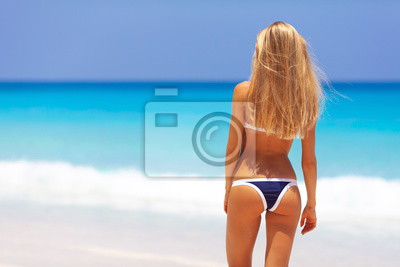 Plakat Travel vacation wallpaper - Beautiful young pretty blonde girl in bikini with white sand on perfect sport sexy body relax in sea of white sand paradise tropical Maldive Seychelles beach on resort