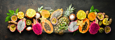 Plakat Tropical fruits on a brown background: papaya, mangosteen, cactus fruit, pytahaya, pineapple. Top view. Free space for text.
