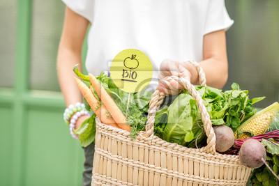 Plakat Trzymając torbę pełną świeżych organicznych warzyw z zielonym naklejką z lokalnego targu na zielonym tle
