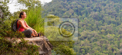 Plakat turysta kobieta siedzi na krawędzi urwiska i korzystających z drewna tropikalnego