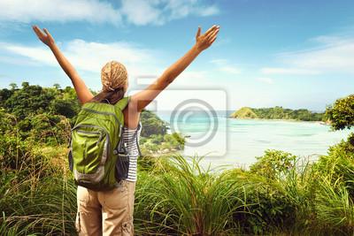 Plakat Turystą z plecak korzystających z widokiem na morze z szczycie góry