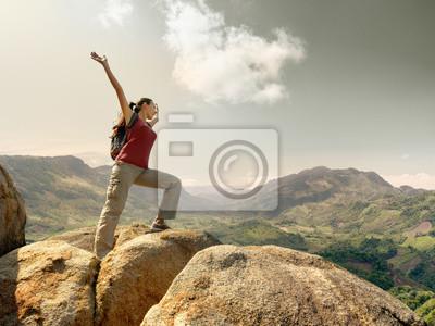 Turystą z plecak stojących na szczycie góry z podniesionym ha