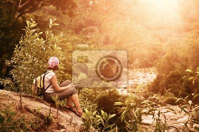 Turysta z plecakiem siedzieć i relaks korzystających wschód słońca