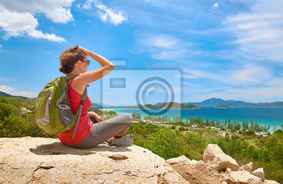 Turysta z plecakiem siedzieć na skale na tle jasnego nieba