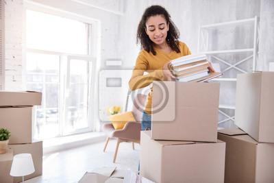 Plakat Ulubione książki. Przyjemna dziewczyna o kręconych włosach pakuje stos książek w duże pudło, zanim wyniesie się z pokoju w akademiku