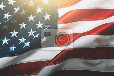 Plakat USA flag background. Waving American flag in sunlight flare, close up