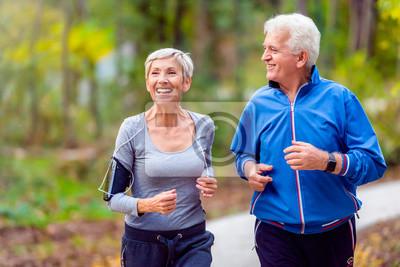 Plakat Uśmiechnięta starsza aktywna para jogging wpólnie w parku
