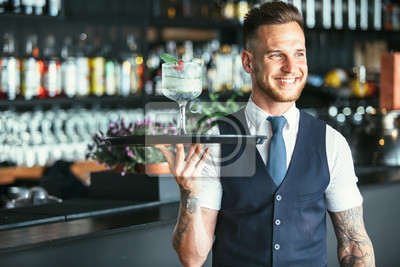 Plakat Uśmiechnięty kelner przygotowywający słuzyć koktajl