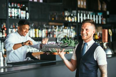 Plakat Uśmiechnięty kelner z koktajlem