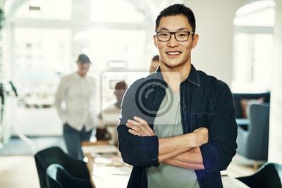 Plakat Uśmiechnięty młody Azjatycki projektant z kolegami pracuje w tle