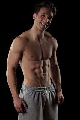 Plakat uśmiechnięty, półnagi mężczyzna mięśni na czarnym tle