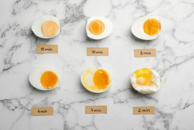 Plakat Various types of boiled eggs on marble background, flat lay. Cooking time