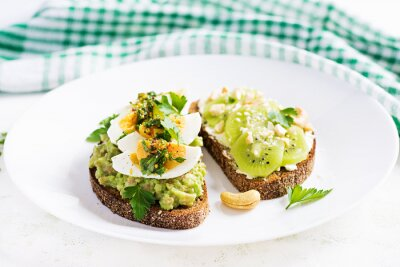 Vegetarian breakfast. Sandwich with avocado puree, boiled eggs and sandwich cream cheese, kiwi, nuts.  Healthy breakfast or lunch.