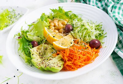 Vegetarian salad Buddha bowl dish with chickpea, avocado,  cucumber, carrot, chia seeds,  lettuce salad and olives. Healthy eating trend, superfood.