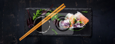 Vegetarian vietnamese spring rolls with spicy sauce, carrot, cucumber, red cabbage and rice noodle. Vegan food. Tasty meal.  Top view, flat lay, banner