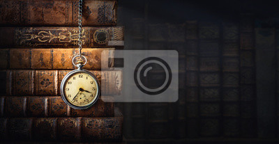 Plakat Vintage clock hanging on a chain on the background of old books. Old watch as a symbol of passing time. Concept on the theme of history, nostalgia, old age. Retro style.