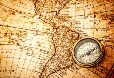 Plakat Vintage compass lies on an ancient world map.