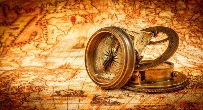 Plakat Vintage Kompas leży na starożytnej mapie świata.