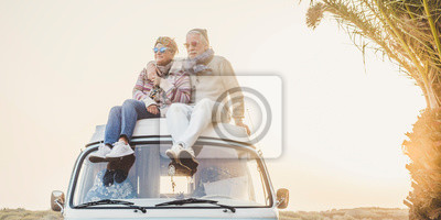 Plakat Wanderlust and travel destination happiness concept with old senior beautiful couple sitting and enjoying the outdoor freedom on the roof of vintage van vehicle together - sun backlight
