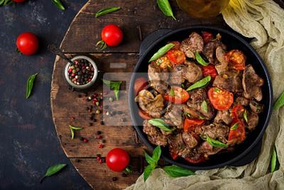 Wątróbka drobiowa (podroby) z cebulą i pomidorami na patelni w języku ormiańskim. Płaskie leże. Widok z góry