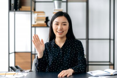 Plakat Webcam headshot of a positive pretty, smart confident young asian woman, freelancer or manager, sits at work desk, talking with colleagues or friends via video link, waving hand, smiling friendly