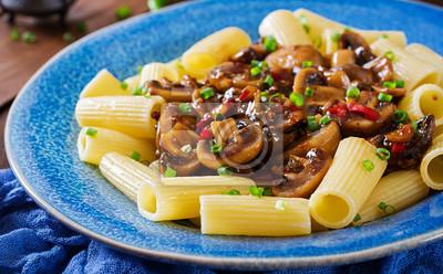 Wegetariański makaron rigatoni z pieczarkami i papryką chili w niebieskim misce na drewnianym stole. Wegańskie jedzenie.