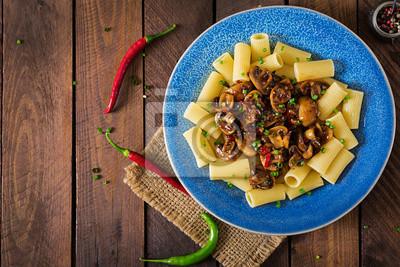 Wegetariański makaron rigatoni z pieczarkami i papryką chili w niebieskim misce na drewnianym stole. Wegańskie jedzenie. Leżał płasko. Widok z góry