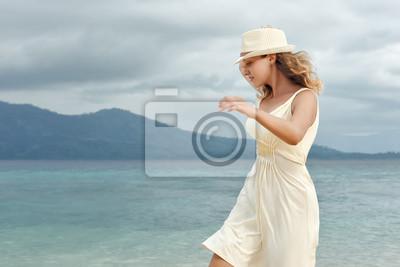 Wesoła kobieta na sobie białą sukienkę na plaży na tle dramatycznego nieba