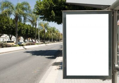 Plakat White blank vertical billboard at the bus stop on the city street. In the background of buses and roads. Sketch. Poster on the street next to the road.