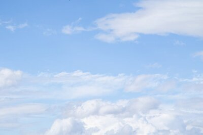 Plakat White clouds in the blue sky. Clouds are suspended in the atmosphere condensation of water vapor.