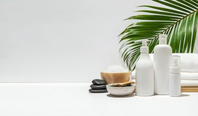 Plakat White cosmetic bottles with spa element and towel with palm leaf on white background. Blank label for branding mock-up. Natural beauty product concept. Copy space.