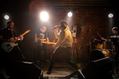 Plakat WIDE Punk rock band playing music during their concert on a stage of small venue. Vocals, guitars and drums. Shot with 2x anamorphic lens