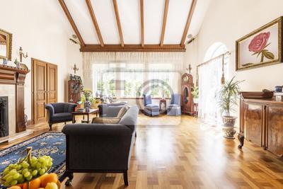 Plakat Widok luksusowego wnętrza salonu z wysokim sufitem, drewnianą podłogą, słonecznymi oknami i klasyczną sofą, fotelami i szafką. Pusta przestrzeń na podłodze. Prawdziwe zdjęcie.
