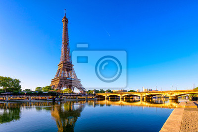 Plakat Widok wieża eifla i rzeka wonton przy wschodem słońca w Paryż, Francja. Wieża Eiffla jest jednym z najbardziej znanych zabytków Paryża