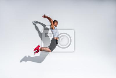 Plakat widok z boku młodego sportowca african american skoków na szaro