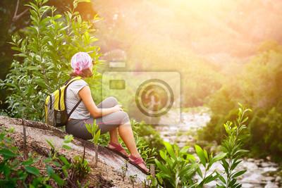 Widok z plecakiem siedzieć i relaks korzystających zachód słońca