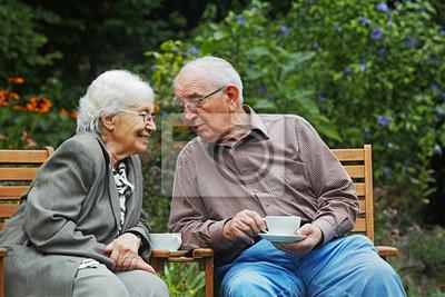 Plakat wieku para na ławce w ogrodzie