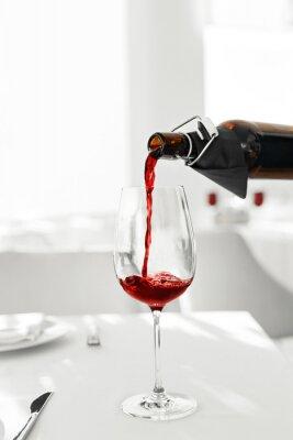 Plakat Wino. Zamknij Się Wlewanie wina czerwonego z butelki do wina szkła w restauracji. Napoje alkoholowe. Świętowanie i stylu życia.