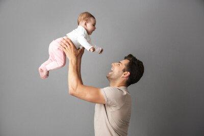 Plakat Wizerunek szczęśliwy ojca mężczyzna trzyma jego małego dziecka w rękach, odosobniony nadmierny szary tło