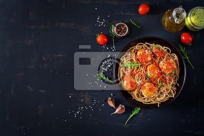 Włoski makaron. Spaghetti z klopsikami i parmezanem w czarnym talerzu na ciemnym nieociosanym drewnianym tle. Obiad. Widok z góry. Koncepcja slow food