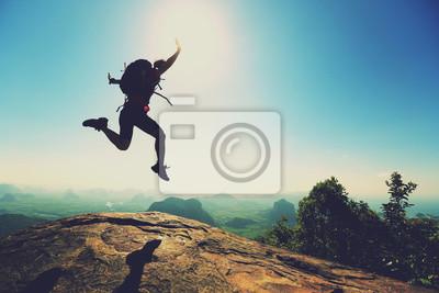 Plakat Wolność kobieta backpacker skoków na szczycie góry sunrise